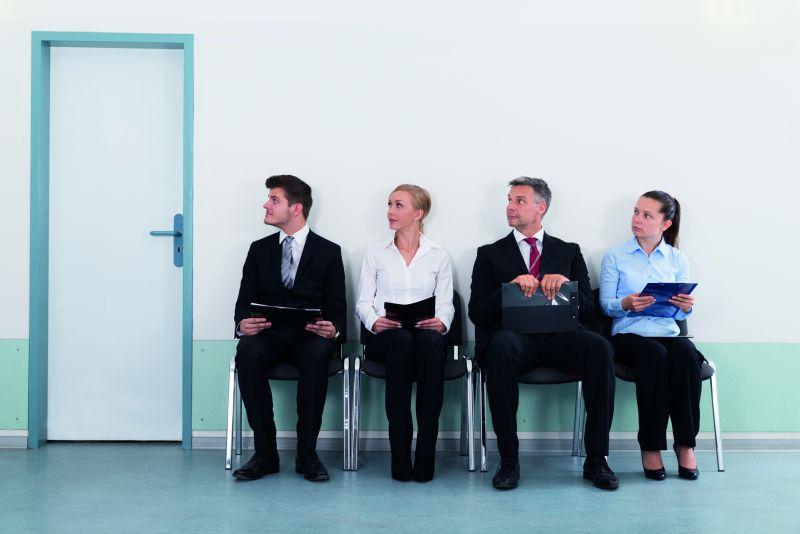 Zwei Männer und zwei Frauen sitzen in einer Stuhlreihe auf einem Flur und halten Bewerbungsunterlagen in den Händen (Bundesweiter Bewerbertag)