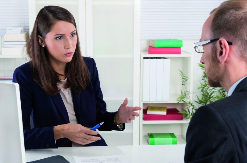 Eine Frau interviewt einen Mann in einem Bewerbungsgespräch (Bundesweiter Bewerbertag).