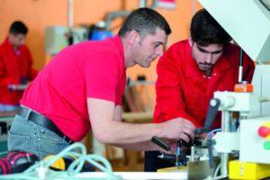 Zwei Arbeitnehmer arbeiten gemeinsam an einer Maschine (Zeitarbeit).