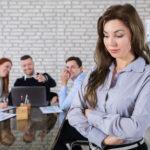 Junge Frau steht vor dem Konferenztisch und ist genervt. (Bürosprüche)