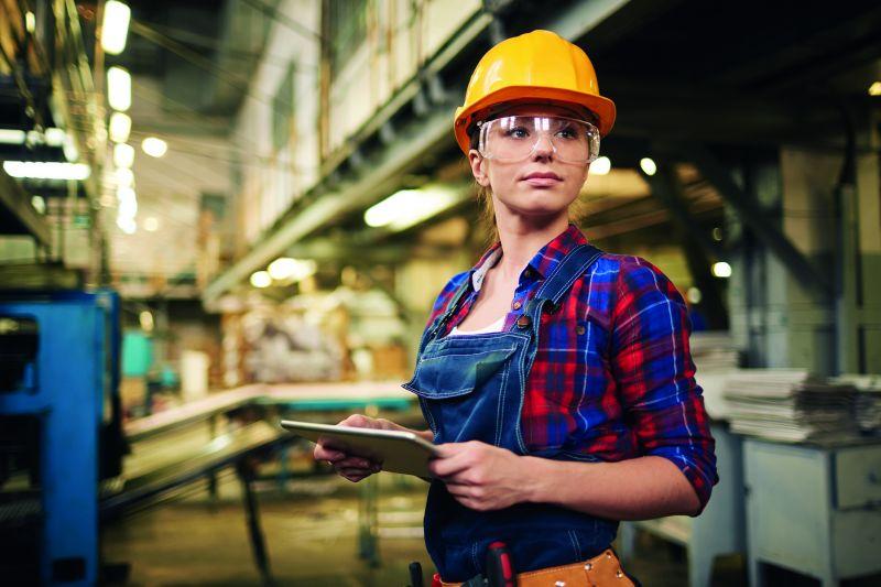 Eine junge Frau trägt Sicherheitskleidung und hält ein Tablet in den Händen (Zeitarbeit).