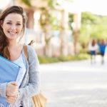 Eine junge Frau lächelt und hält eine Mappe in den Händen (Zeitarbeit).