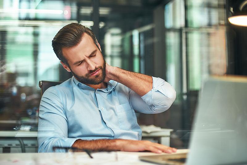 Business Mann sitzt am PC und reibt sich den schmerzenden Nacken. (Zweites Standbein)