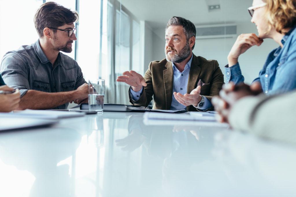 Bürosprüche und leere Phrasen: Chef sitzt mit zwei Mitarbeitern am Konferenztisch.
