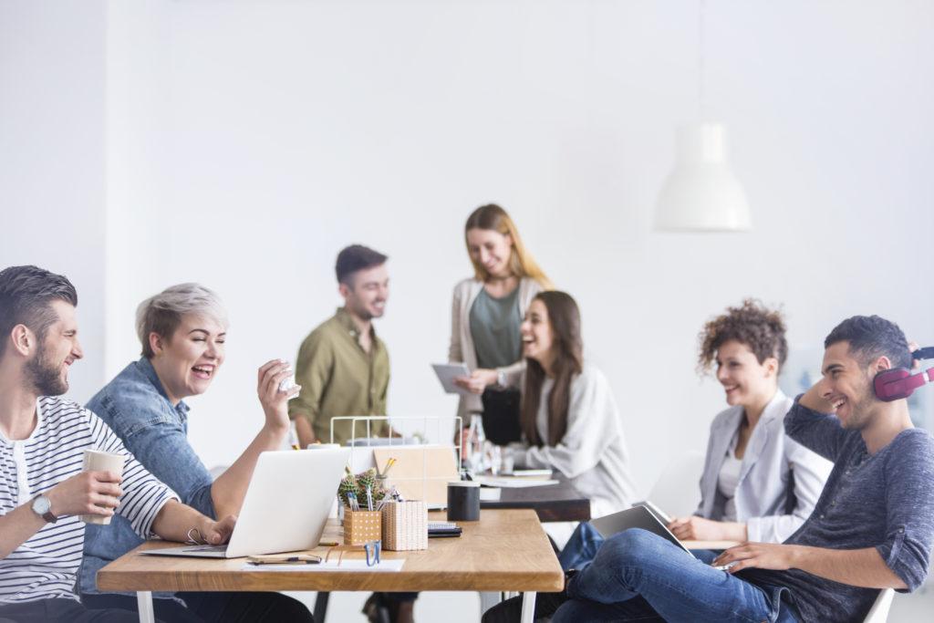 Bürosprüche und leere Phrasen: Team sitzt lachend mit PCs am Schreibtisch.