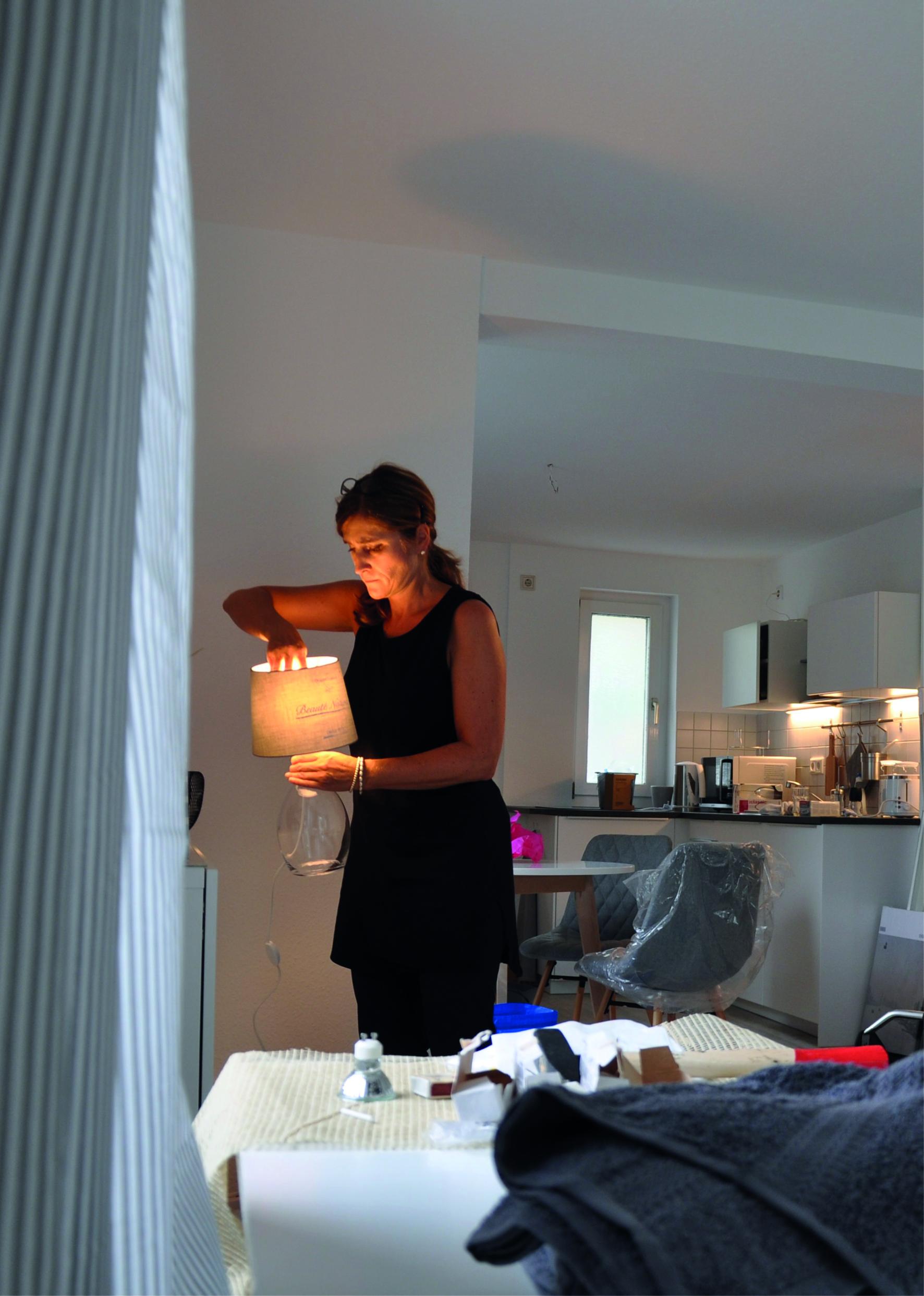 Frau stellt eine Lampe in eine Küche (Home Stager)
