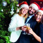 Drei gut gekleidete Arbeitnehmer stehen gemeinsam vor einem geschmückten Tannenbaum, lachen und stoßen mit Sektgläsern an (Weihnachtsfeier im Unternehmen).