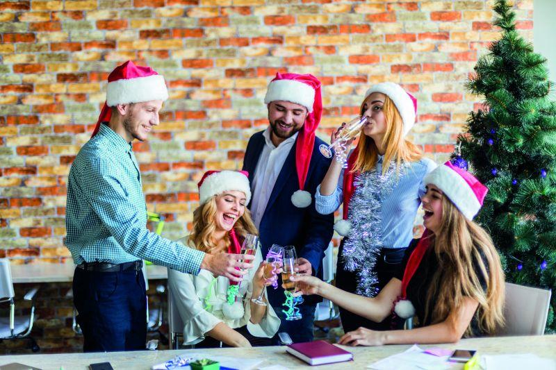 Fünf Arbeitnehmer tragen eine Weihnachtsmütze und stoßen lachend mit Sektgläsern an (Weihnachtsfeier im Unternehmen).