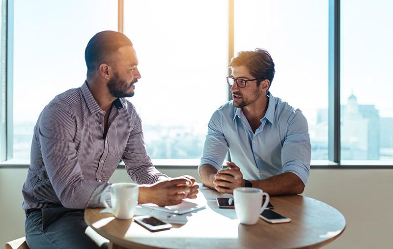 Zwei Männer sitzen gemeinsam an einem Tisch, trinken Kaffee und sprechen miteinander (Konflikte am Arbeitsplatz)