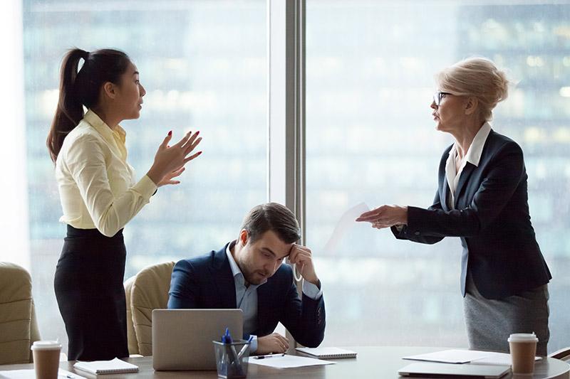 Konflikte am Arbeitsplatz: zwei Frauen stehen sich gegenüber, reden miteinander und gestikulieren wild. Ein Mann sitzt zwischen den beiden Frauen und schaut auf den Tisch.