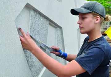 Eine Frau bestimmt mit einem Zollstock die Maße eines Betonstücks (Betonhandwerk).