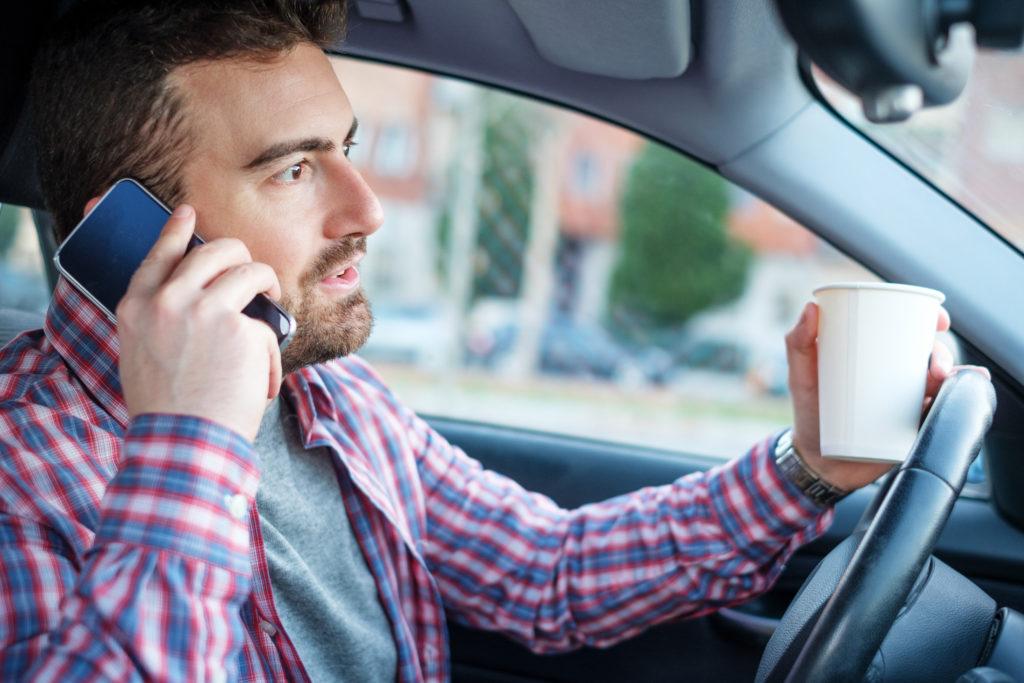Ein Mann telefoniert mit Kaffeetasse in der Hand während er Auto fährt (Ständige Erreichbarkeit)