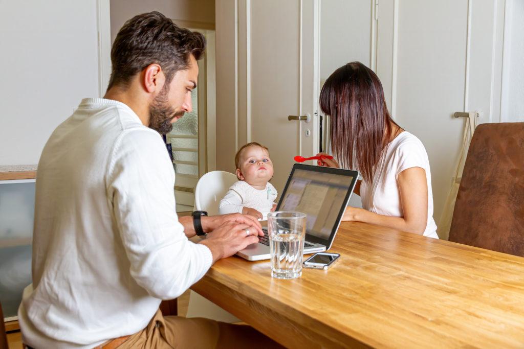 Arbeitnehmer und Corona: Ein Mann arbeitet mit einem Laptop am Tisch. Gegenüber von ihm sitzt eine Frau, die ein kleines Baby füttert.