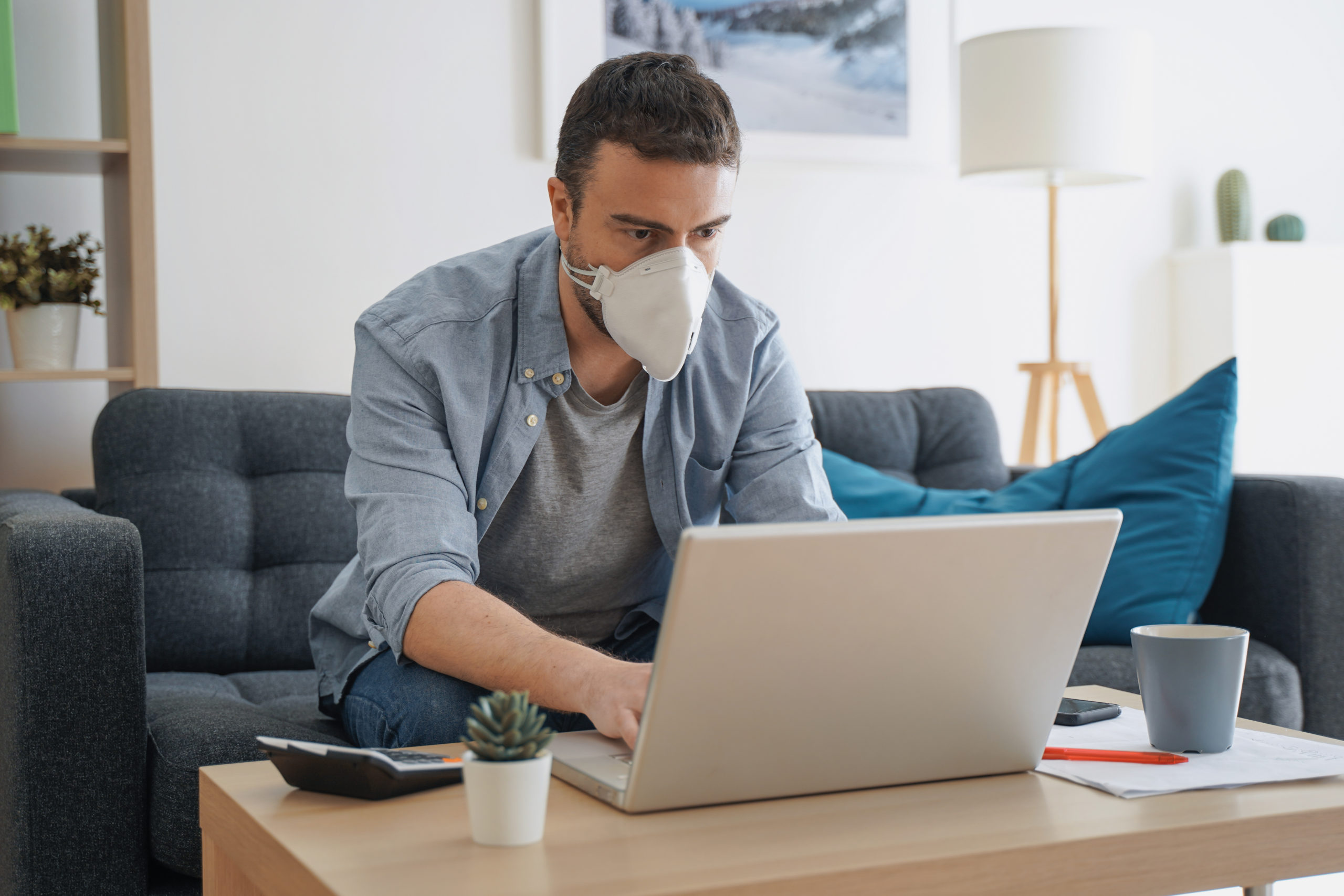 Arbeitnehmer und Corona: Ein Mann trägt einen weißen Mundschutz, sitzt auf dem Sofa und arbeitet am Laptop.