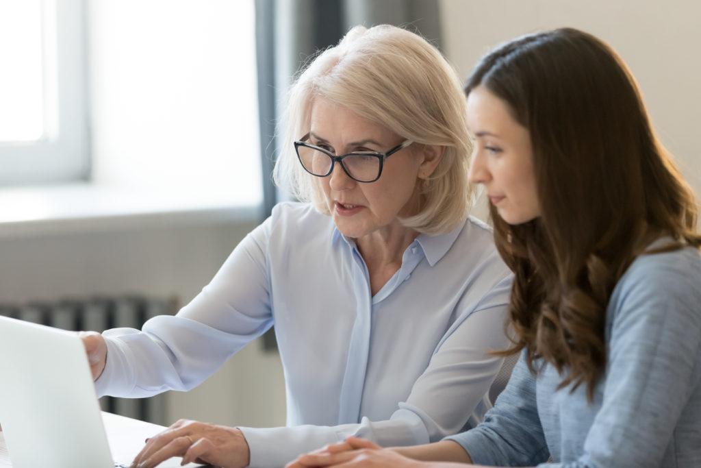 Eine ältere Frau zeigt einer jüngeren Frau etwas auf einem Laptop. (Jobwechsel)
