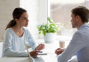 Eine Frau und ein Mann sitzen sich an einem Tisch gegenüber und sprechen miteinander. (Jobwechsel)