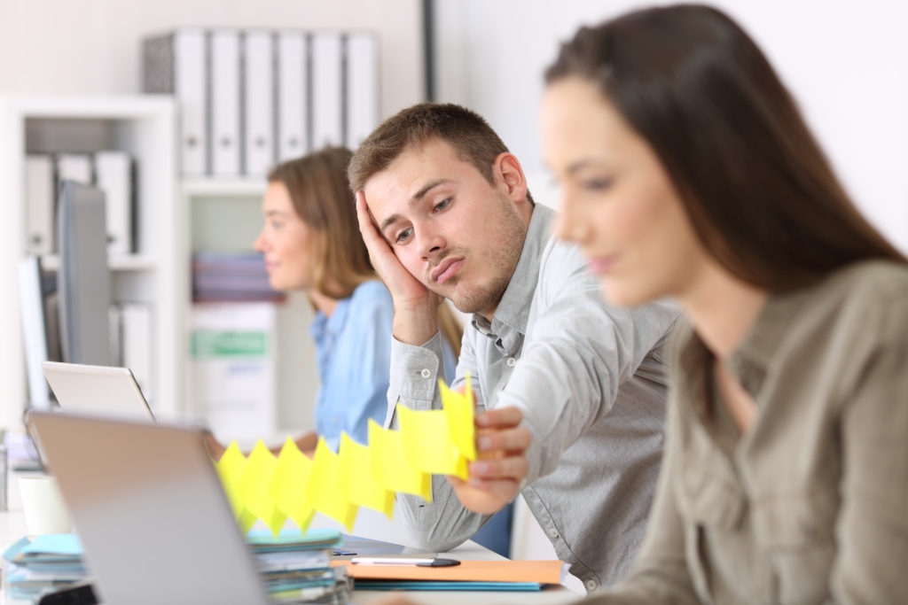 Ein Mann sitzt an einem Schreibtisch, stützt seinen Kopf mit einer Hand und schaut gelangweilt. (Jobwechsel)