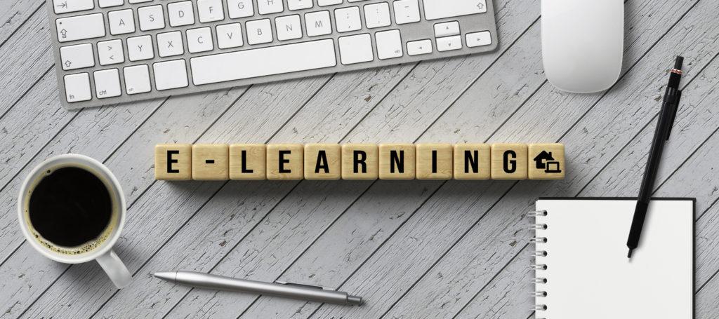 """Ein Schreibtisch mit einer Tastatur und einer Maus. Vor der Tastatur liegen Holzwürfel mit verschiedenen Buchstaben, die das Wort """"E-Learning"""" ergeben (berufliche Weiterbildung online)."""
