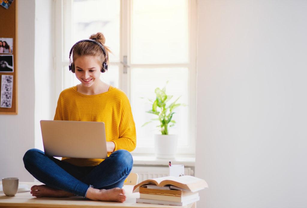 Berufliche Weiterbildung online: eine Frau sitzt auf einem Tisch, mit einem Laptop auf dem Schoß und trägt Kopfhörer.