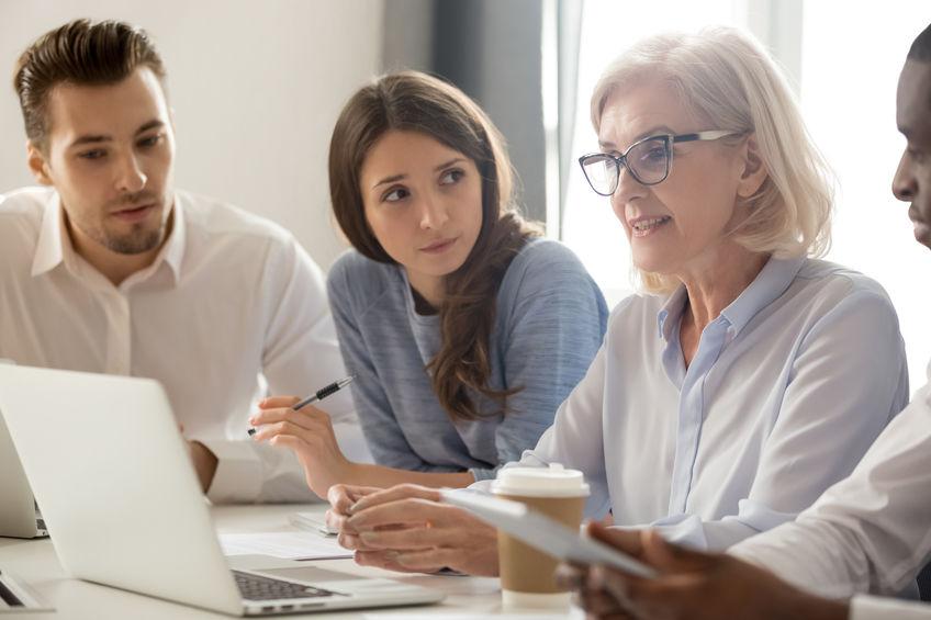 Eine ältere Frau erklärt drei jungen Menschen, die um einen Laptop sitzen, eine Verhandlungsform.